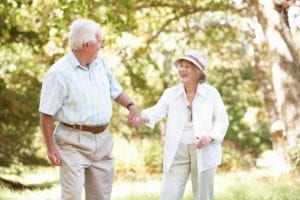 Happy seniors walking in park during Healthy Aging Month